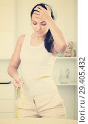 Sad woman measures waist. Стоковое фото, фотограф Яков Филимонов / Фотобанк Лори