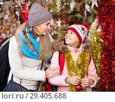 Купить «Happy mother with friendly little daughter buying decorations for Xmas», фото № 29405688, снято 25 мая 2020 г. (c) Яков Филимонов / Фотобанк Лори
