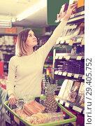 Купить «Girl customer looking for food supplies for week in supermarket», фото № 29405752, снято 23 ноября 2016 г. (c) Яков Филимонов / Фотобанк Лори