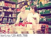 Купить «positive woman with daughter choosing cookies in supermarket», фото № 29405788, снято 5 января 2017 г. (c) Яков Филимонов / Фотобанк Лори