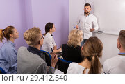 Купить «Young man lecturer answering near whiteboard», фото № 29412540, снято 5 октября 2017 г. (c) Яков Филимонов / Фотобанк Лори