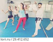 Купить «adults attempting to master new moves during karate class», фото № 29412652, снято 8 апреля 2017 г. (c) Яков Филимонов / Фотобанк Лори