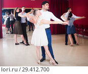 Купить «Ordinary dancing couples enjoying foxtrot», фото № 29412700, снято 24 мая 2017 г. (c) Яков Филимонов / Фотобанк Лори