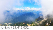 Panorama of the mountains and Aibga Ridge with cable car and low clouds. Remnants of snow and new green grass on Mountains near the ski resort of Rosa Khutor in Krasnaya Polyana. Sochi, Russia. Стоковое фото, фотограф Mikhail Starodubov / Фотобанк Лори