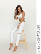 Купить «Attractive young woman in white bra and jeans sits on white background.», фото № 29413320, снято 10 августа 2018 г. (c) Женя Канашкин / Фотобанк Лори
