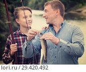 Купить «Adult man with son looking at fish on hook», фото № 29420492, снято 10 декабря 2018 г. (c) Яков Филимонов / Фотобанк Лори