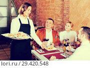Купить «Female waiter carrying order for visitors», фото № 29420548, снято 16 декабря 2018 г. (c) Яков Филимонов / Фотобанк Лори