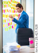 Купить «Young handsome employee with many conflicting priorities», фото № 29421928, снято 15 августа 2018 г. (c) Elnur / Фотобанк Лори