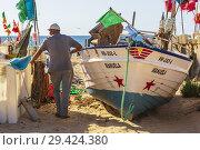 Купить «Local fisherman standing beside his fishing boat, at sunset, on the beach at Monte Gordo, Algarve, Portugal.», фото № 29424380, снято 7 октября 2018 г. (c) age Fotostock / Фотобанк Лори