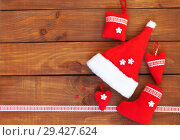 Купить «New Year's still life. Traditional red Christmas handmade toys on a wooden background: Santa's hat, hearts and a gift sock. Free space for text and congratulations», фото № 29427624, снято 10 декабря 2017 г. (c) Виктория Катьянова / Фотобанк Лори