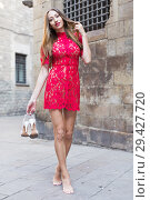 Купить «portrait of young female in sexually red gown with pumps in hands standing in town», фото № 29427720, снято 24 июня 2017 г. (c) Яков Филимонов / Фотобанк Лори
