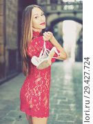 Купить «portrait of sexy young woman in red dress walking with shoes in hand in the old city», фото № 29427724, снято 24 июня 2017 г. (c) Яков Филимонов / Фотобанк Лори