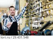 Купить «Worker displaying result of his key forming in workplace», фото № 29431548, снято 2 февраля 2017 г. (c) Яков Филимонов / Фотобанк Лори