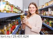 Купить «Positive woman customer holding pickle goods in food store», фото № 29431624, снято 11 апреля 2018 г. (c) Яков Филимонов / Фотобанк Лори