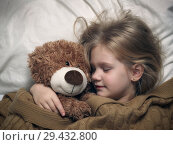 Купить «A little girl is sleeping with a toy bear. The child smiles in his sleep», фото № 29432800, снято 16 ноября 2018 г. (c) Ирина Козорог / Фотобанк Лори