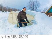 Купить «A man sheds snow from a greenhouse with a shovel on a snowy cottage.», фото № 29439140, снято 19 февраля 2017 г. (c) Акиньшин Владимир / Фотобанк Лори
