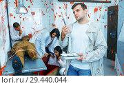 Купить «Focused guy in escape room with traces of blood», фото № 29440044, снято 8 октября 2018 г. (c) Яков Филимонов / Фотобанк Лори