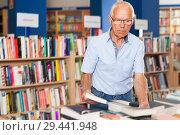 Купить «bespectacled senior male customer visiting bookshop in search of interesting fiction», фото № 29441948, снято 11 июня 2018 г. (c) Яков Филимонов / Фотобанк Лори