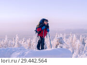 Male hiker with a backpack struggles to climb a snow-covered mountain with trekking poles in a winter frosty landscape. Стоковое фото, фотограф Евгений Харитонов / Фотобанк Лори
