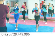 Купить «group of women and their trainer are boxing in gym», фото № 29449996, снято 8 октября 2017 г. (c) Яков Филимонов / Фотобанк Лори