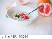 Купить «sweet oatmeal with slices of red grapefruit in a ceramic bowl», фото № 29450580, снято 20 ноября 2018 г. (c) Peredniankina / Фотобанк Лори