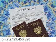 Бланк брачного договора и два российских паспорта лежат на новых купюрах. Стоковое фото, фотограф Наталья Гармашева / Фотобанк Лори