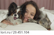 Купить «Happy teen girl communicates with dog Papillon and Thai cat in bed», фото № 29451104, снято 22 июля 2019 г. (c) Юлия Машкова / Фотобанк Лори