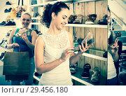 Купить «Young woman choosing a pair of shoes», фото № 29456180, снято 9 декабря 2018 г. (c) Яков Филимонов / Фотобанк Лори