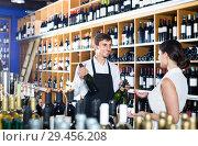 Купить «portrait of male seller showing bottle of wine to female customer in wine shop», фото № 29456208, снято 6 июня 2020 г. (c) Яков Филимонов / Фотобанк Лори