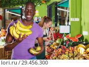 Купить «man standing with banana in the fruit market.», фото № 29456300, снято 26 мая 2018 г. (c) Яков Филимонов / Фотобанк Лори