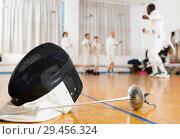 Купить «Closeup of fencing mask and rapier on floor in gym», фото № 29456324, снято 30 мая 2018 г. (c) Яков Филимонов / Фотобанк Лори