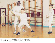 Купить «Focused boys fencers attentively listening to professional fencing coach in gym», фото № 29456336, снято 30 мая 2018 г. (c) Яков Филимонов / Фотобанк Лори