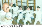 Купить «Adult man fencer practicing effective fencing techniques in training room», фото № 29456340, снято 30 мая 2018 г. (c) Яков Филимонов / Фотобанк Лори