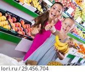 Купить «Mother with girl showing thumbs up in supermarket», фото № 29456704, снято 19 ноября 2019 г. (c) Яков Филимонов / Фотобанк Лори