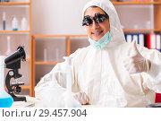 Купить «Young biochemist wearing protective suit working in the lab», фото № 29457904, снято 11 августа 2018 г. (c) Elnur / Фотобанк Лори