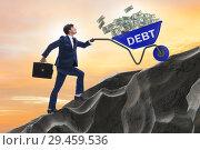 Купить «Businessman pushing wheelbarrow uphill in debt loan concept», фото № 29459536, снято 22 ноября 2018 г. (c) Elnur / Фотобанк Лори