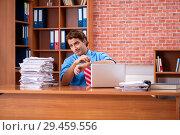 Купить «Young employee with excessive work sitting at the office», фото № 29459556, снято 29 августа 2018 г. (c) Elnur / Фотобанк Лори
