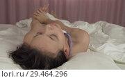 Купить «Beautiful teen girl wakes up in bed and smiles stock footage video», видеоролик № 29464296, снято 7 ноября 2018 г. (c) Юлия Машкова / Фотобанк Лори