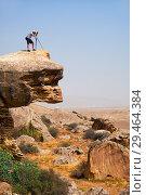 Купить «Photographer with tripod on the overhanging over plane rock cliff. Gobustan, Azerbaijan», фото № 29464384, снято 10 сентября 2018 г. (c) Serg Zastavkin / Фотобанк Лори
