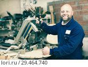 Купить «Woodworker on lathe in workroom», фото № 29464740, снято 25 мая 2019 г. (c) Яков Филимонов / Фотобанк Лори