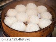 Купить «A vendor prepares Baozi (Bao) steamed buns at the Jalan Petaling Street market, Chinatown, Kuala Lumpur, Malaysia.», фото № 29469876, снято 17 июня 2018 г. (c) age Fotostock / Фотобанк Лори