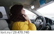 Купить «A young woman in yellow jacket sits on the driver's seat, puts down the visor and looks in the mirror, fixing her hair under the hat», видеоролик № 29470740, снято 22 февраля 2020 г. (c) Константин Шишкин / Фотобанк Лори