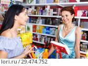 Купить «Smiling saleswoman helping to girl client with purchases in salon», фото № 29474752, снято 21 июня 2018 г. (c) Яков Филимонов / Фотобанк Лори