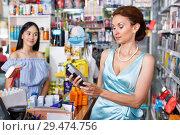 Купить «Saleswoman helping to client with payments in salon», фото № 29474756, снято 21 июня 2018 г. (c) Яков Филимонов / Фотобанк Лори