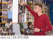 Купить «Serious male choosing DVD in store attentively reading contents», фото № 29475008, снято 15 февраля 2018 г. (c) Яков Филимонов / Фотобанк Лори