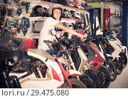Купить «Portrait of glad male in helmet on motorbike in the store», фото № 29475080, снято 17 июля 2017 г. (c) Яков Филимонов / Фотобанк Лори