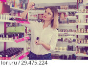 Купить «Girl shopping in cosmetics store, choosing new nail polishes», фото № 29475224, снято 31 января 2018 г. (c) Яков Филимонов / Фотобанк Лори