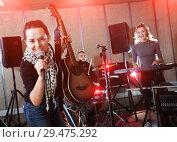 Купить «Attractive female soloist playing guitar and singing with her mu», фото № 29475292, снято 26 октября 2018 г. (c) Яков Филимонов / Фотобанк Лори
