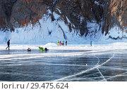 Купить «Baikal Lake. A group of tourists travels around Olkhon Island near Khoboy Cape and take pictures of beautiful icicles and blue ice», фото № 29475624, снято 8 марта 2015 г. (c) Виктория Катьянова / Фотобанк Лори