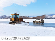 Купить «Lake Baikal. Winter road to Olkhon Island over the ice of the Small Sea (Maloe More). Bulldozer clears ice crossing from snow», фото № 29475628, снято 26 февраля 2017 г. (c) Виктория Катьянова / Фотобанк Лори